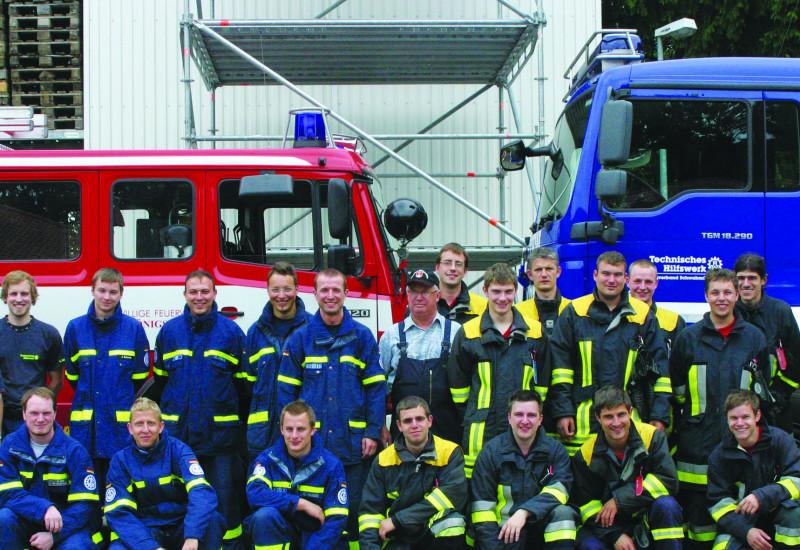 Einsatzkräfte in Uniformen des THW und einer Feuerwehr als Gruppenfoto vor ihren Einsatzfahrzeugen.