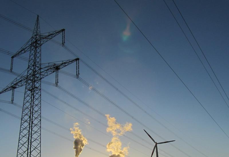 Übertragungsmasten mit Hochspannungsleitungen, Windräder und konventionelles Kraftwerk vor Sonnenuntergang.