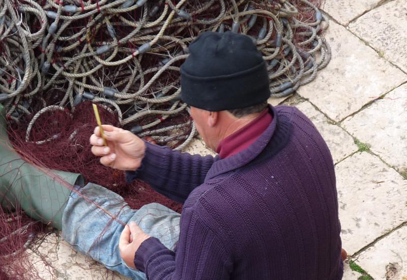 Rückenaufnahme eines Fischers, der Netze repariert.