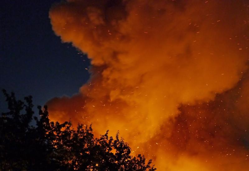 Feuerschein vor Nachthimmel im Vordergrund Umrisse von Laubbäumen.