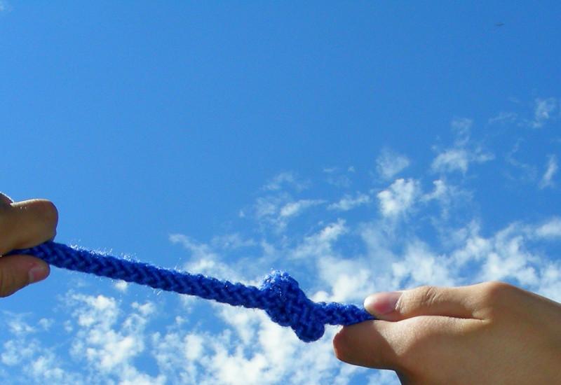Blaues Seil mit Knoten an dem von Händen in verschiedene Richtungen gezogen wird.