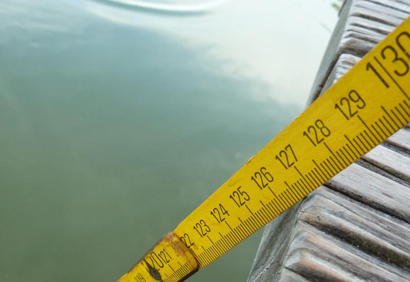 Nahaufnahme gelber Zollstock, der von einem Bootssteg ins Wasser reicht.