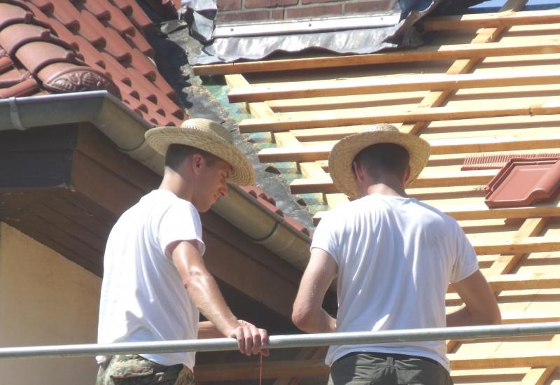Zwei Männer mit Strohhüten auf Baugerüst beim Decken eines Daches.