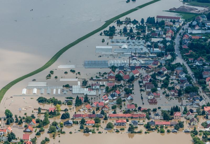 Luftaufnahme einer stark überschwemmten Siedlung hinter einem Deich.