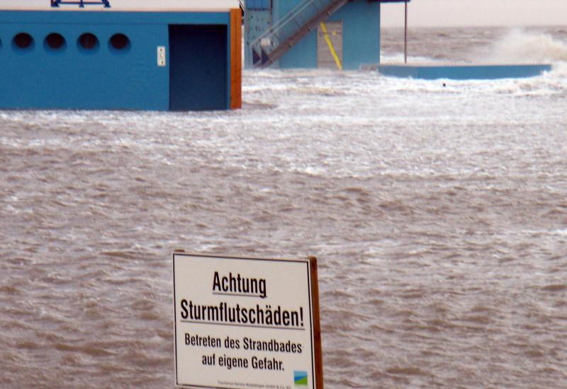 Warnschild vor Sturmflutschäden in überfluteter Hafenanlage.