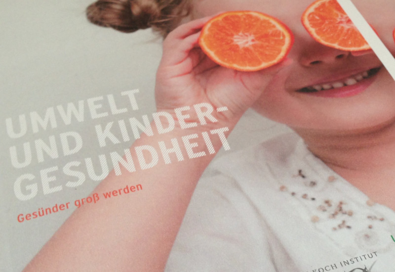 Cover of the brochure with a photo of a little girl holding two halves of an orange in front of her eyes to make fun