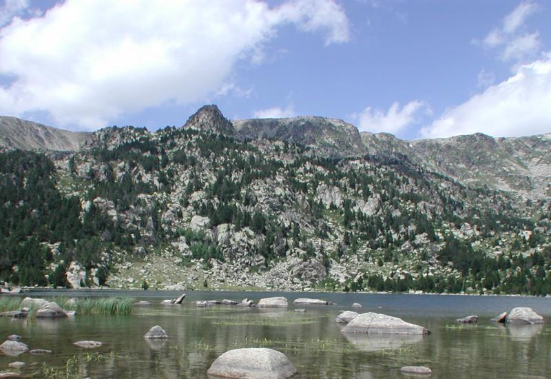 Ein See umgeben von Bergen mit klarem Wasser