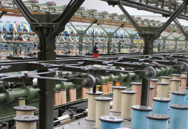 Die Mechanik einer Spinnerei mit vielen hintereinander aufgereihten Garnrollen in blau und beige