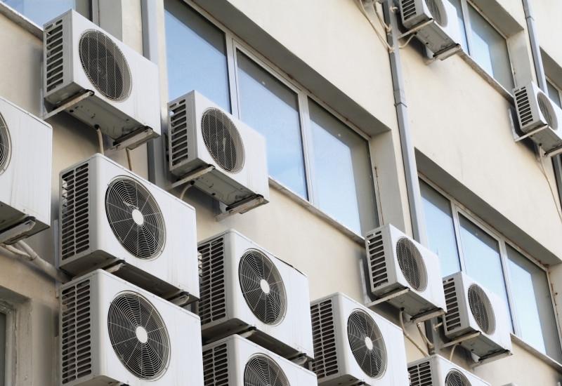 Viele kleine Klimaanlagen, die außen an einem Gebäude angebracht sind.