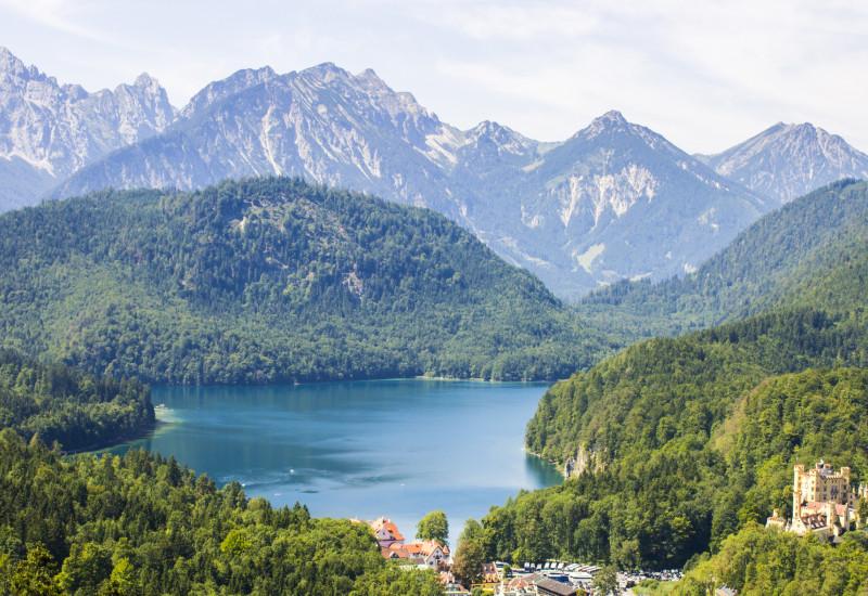 Blick auf einen Bergsee mit Bergen darum und einem blauen Himmel.