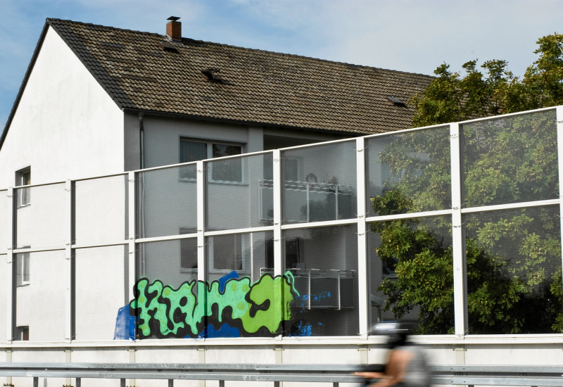 Ein grauer Hauseingang mit einer Bushaltestelle