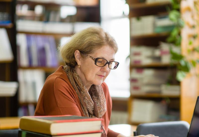 Eine Frau sitzt mit einem Laptop in einer Bibliothek und liest ein Buch.