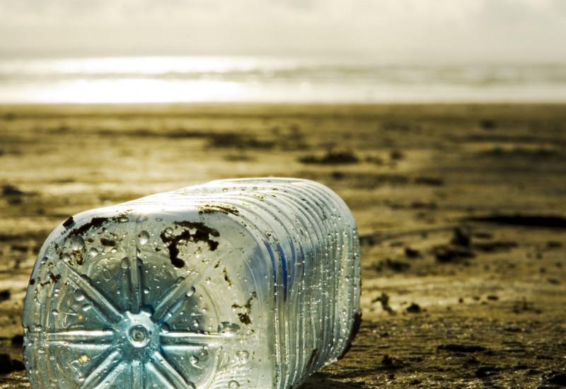 Eine Plastikflasche liegt am Strand.