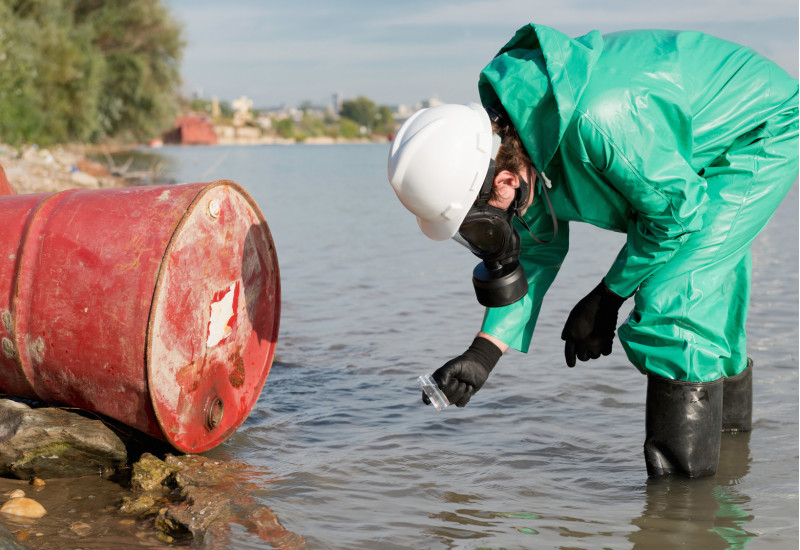 A red barrel lies in a river and is examined by a person in a green protective suit.