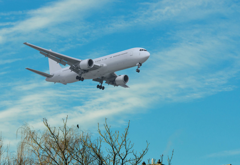 Ein Flugzeug fliegt über ein Wohngebiet.