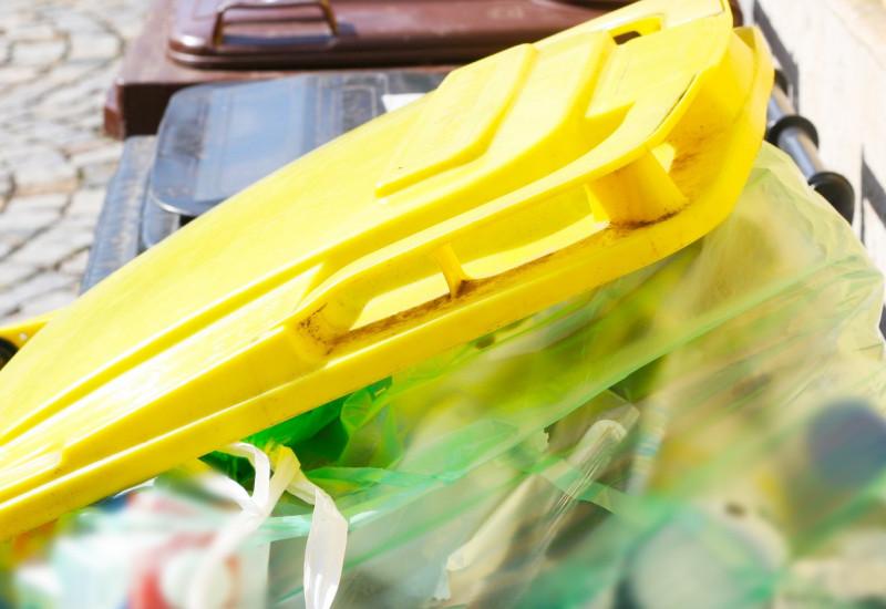 Eine geöffnete gelber Mülltonne, in der Plastikmüll zu sehen inst.