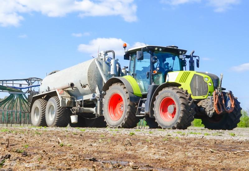 Ein Traktor bringt Gülle auf einem Feld aus