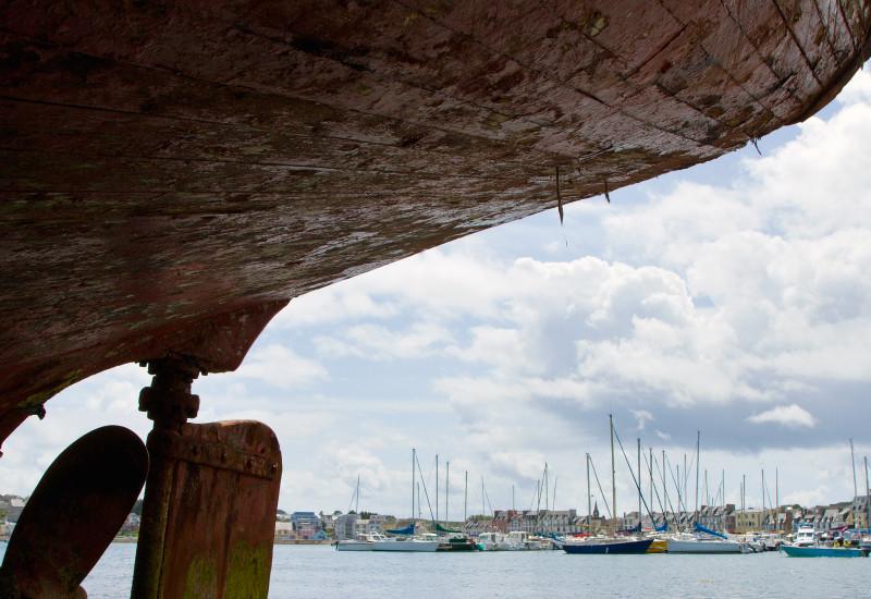 Ein Bootsrumpf und im Hintergrund ein Yachthafen.