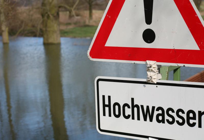 """Ein Schild mit der Aufschrift """"Hochwasser""""."""