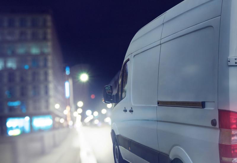 Ein Lieferwagen fährt bei Dunkelheit durch eine Stadt.