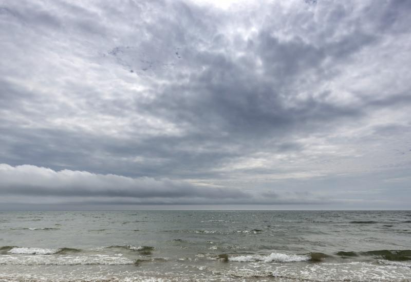 Ein Strand mit Wellen und Meer.