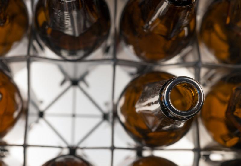 Eine Kiste mit leeren Bierflaschen von oben.