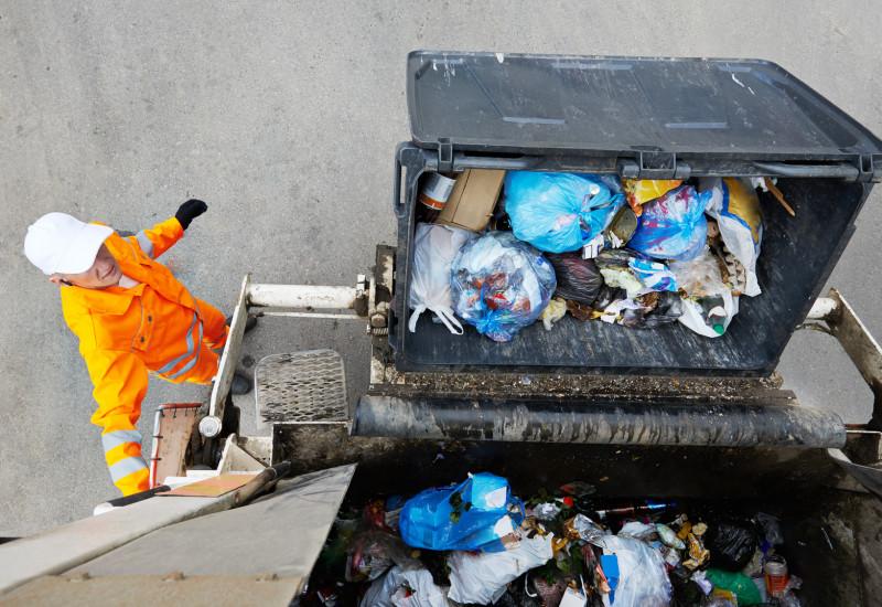 Ein Müllcontainer wird in einen Müllwagen gekippt.