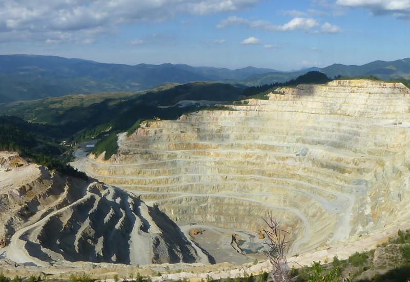 Vorne ist ein Steinbruch zu sehen, dahinter Hügel und blauer Himmel mit einigen Wolken.
