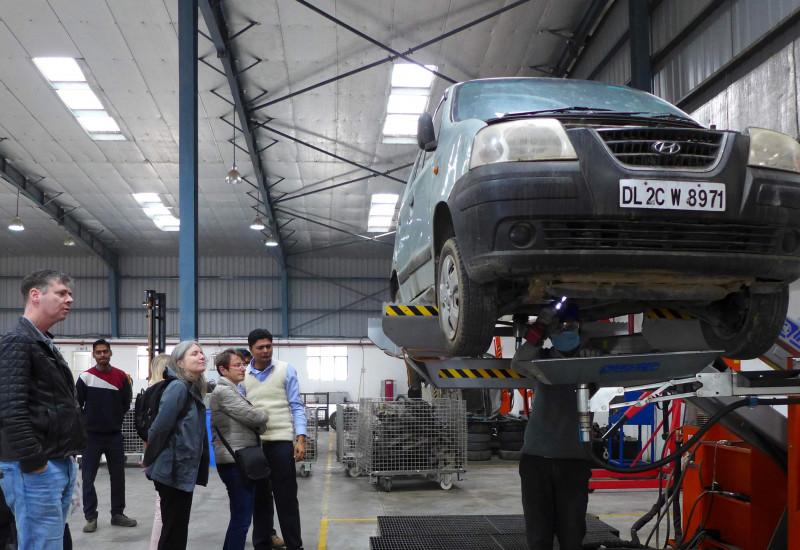 Ein Auto in einer Werkstatt auf einer Hebebühne, daneben stehen mehrere Personen