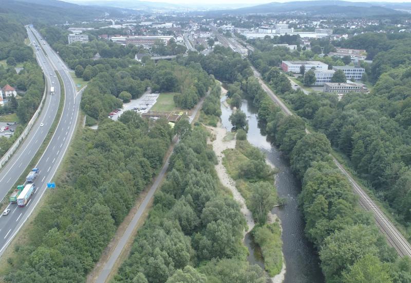 Ein renaturierter Fluss in der Mitte, links eine Autobahn, rechts Bahngleise.