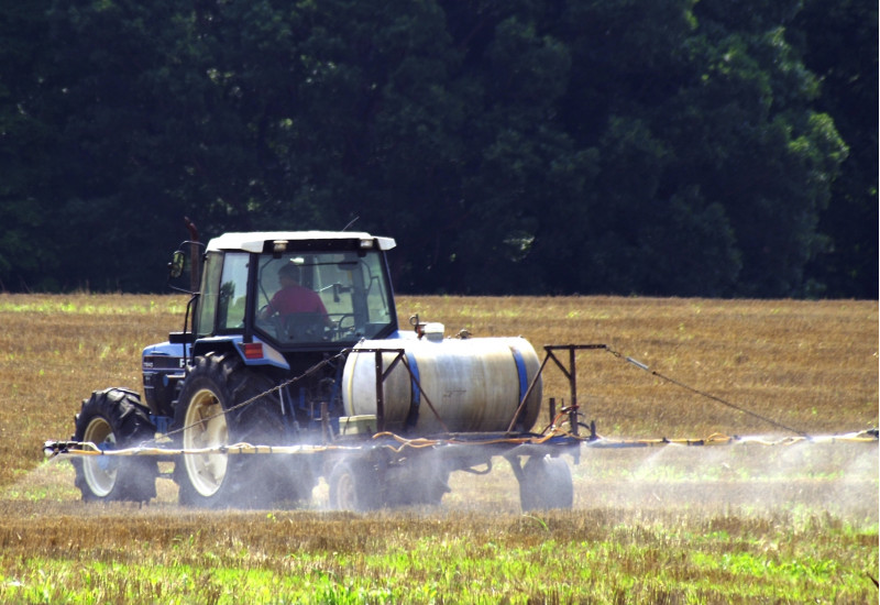 Ein Traktor sprüht Pflanzenschutzmittel auf ein Feld.