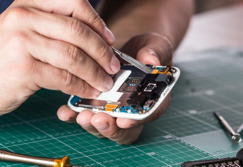 Eine Hand hält ein Smartphone, welches repariert wird.