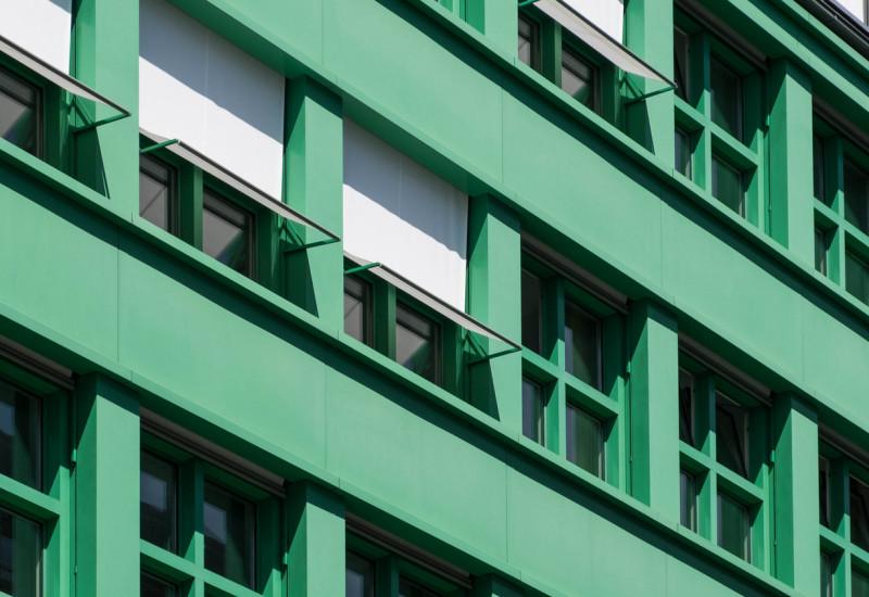 Eine Hausfassade mit Fenstern, die beschattet werden.