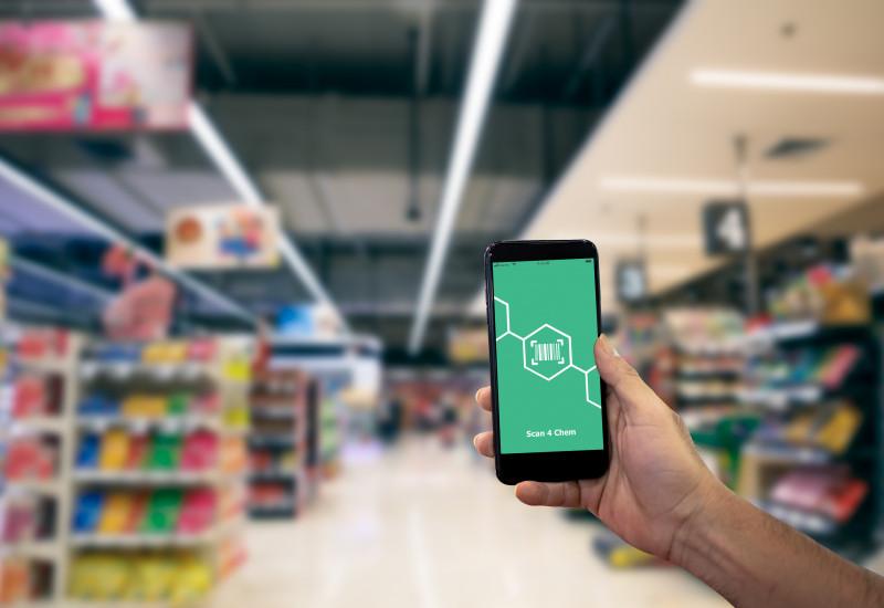 Eine Hand hält ein Smartphone in einem Geschäft
