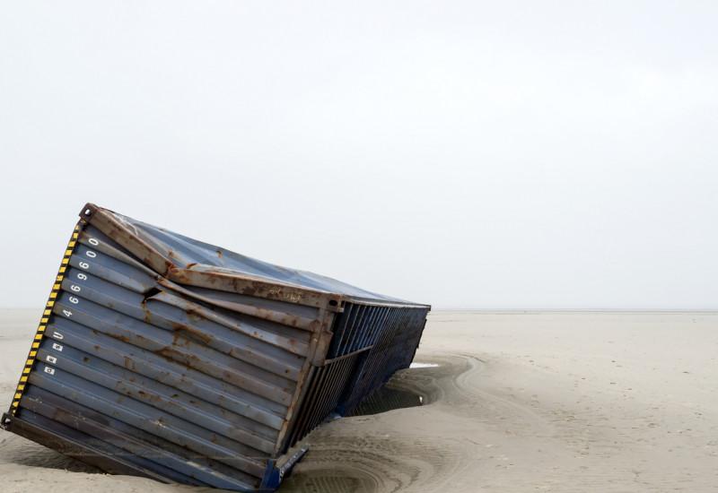 Ein havarierter Schiffscontainer liegt an einem Sandstrand.