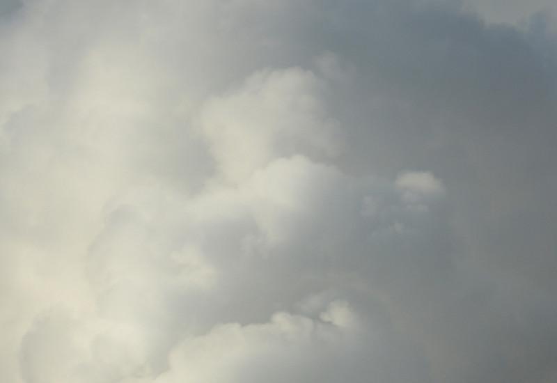 Ein rauchender Schornstein vor bewölktem Himmel.