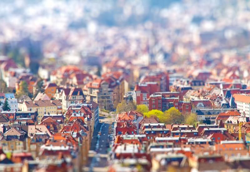 Eine Stadt aus der Luft, es sind Dächer und eine Straße zu sehen.