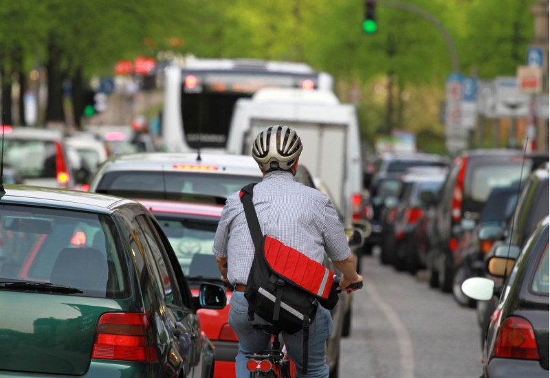 Ein Fahrradfahrer in einem Stau mit Autos