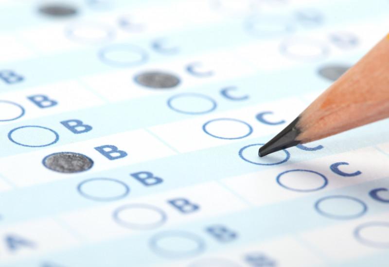 Ein Bleistift kreuzt auf einem Fragebogen Kästchen an.