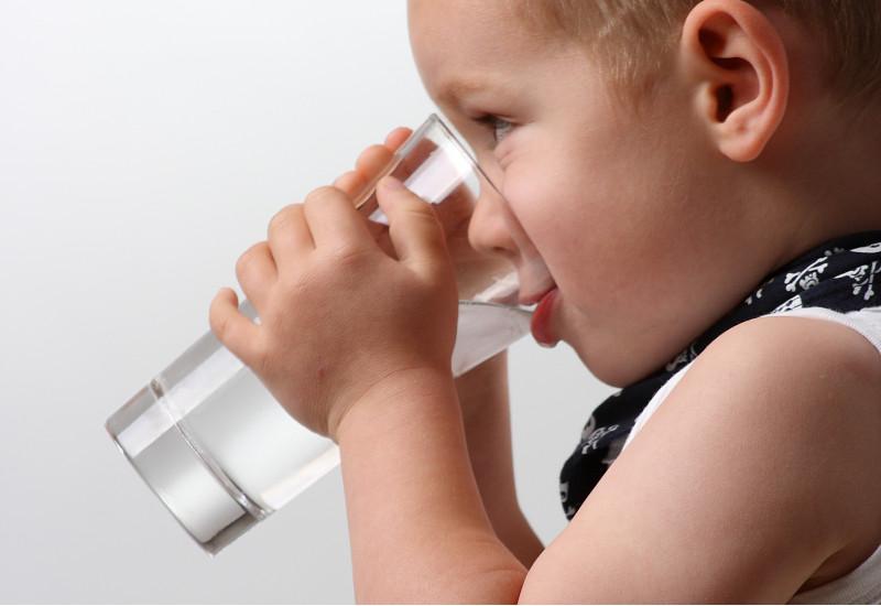 Ein Kind trinkt aus einem Glas.