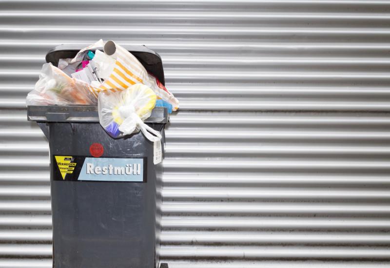 Eine überquellende Abfalltonne vor einem silberfarbenen Tor.