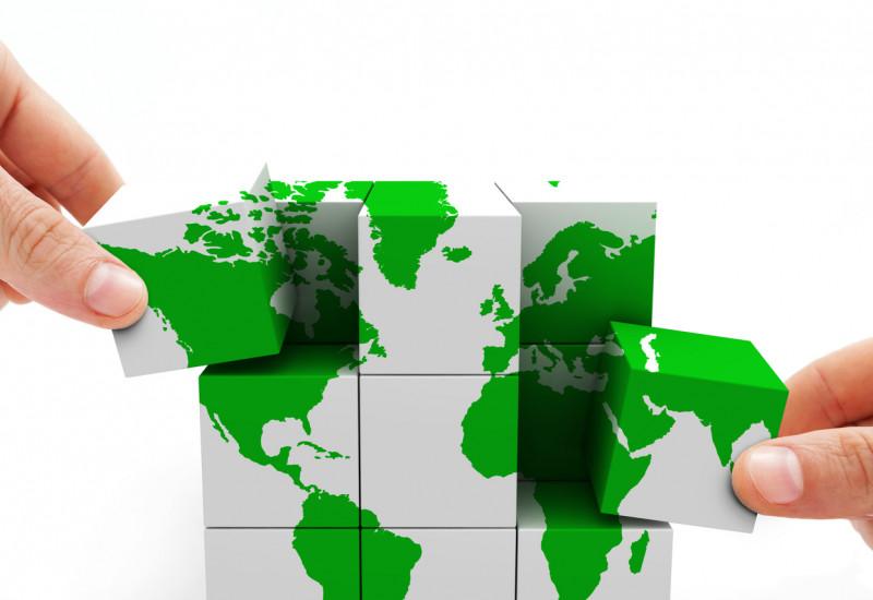 Zwei Hände mit Würfeln, die die Weltkarte abbilden.