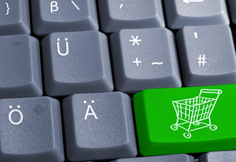 A computer keybord with a green button with a shopping cart.