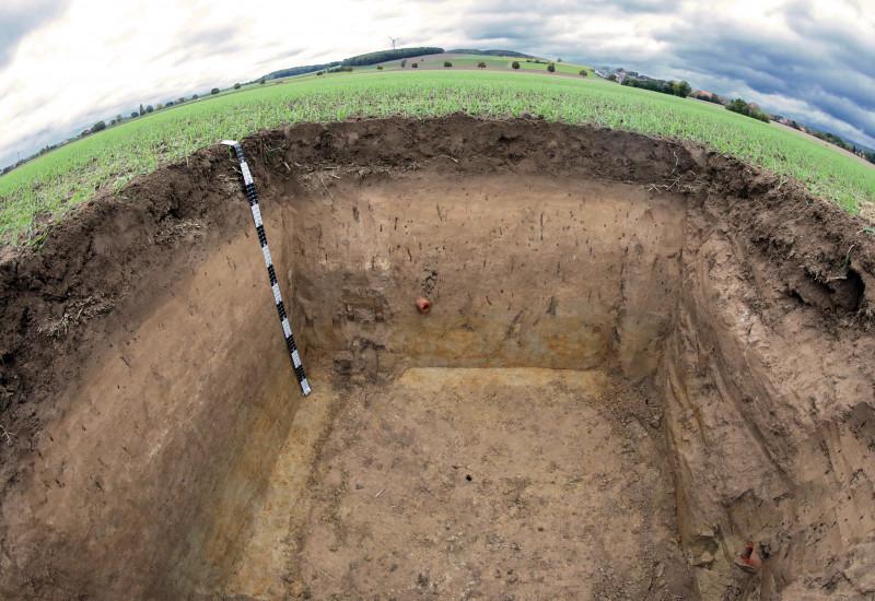 Großes ausgehobenes Loch auf einer Wiese; Bodenprofil vom Lössboden zu sehen