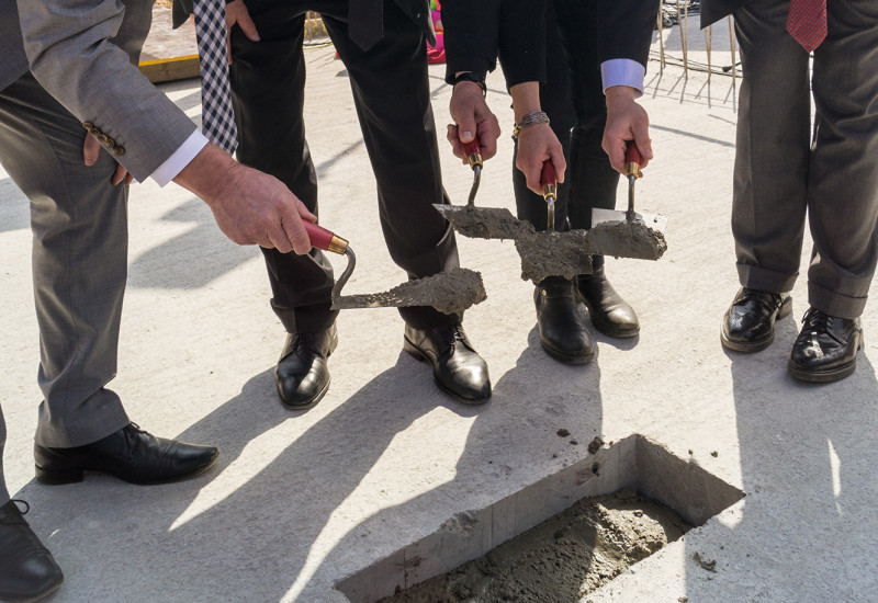 a hole in a baseplate for a building is filled with concrete by three men and a women who are all well-dressed
