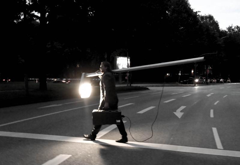 Mann mit leuchtender Laterne läuft über eine Straße.