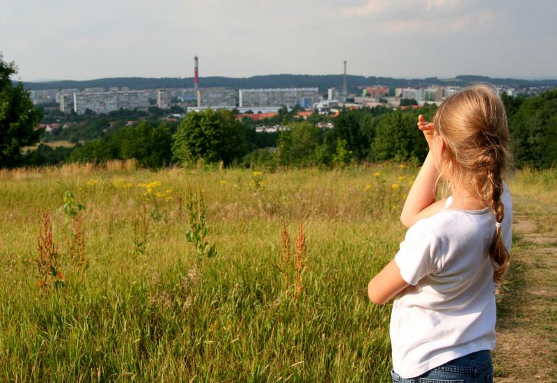 Kind auf einem Feld schau auf die entfernte Stadt.