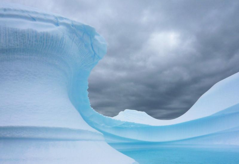 Vor dunkel bewölktem Himmel ragt ein weiß-blauer Eisberg auf. Er ist geschwungen. Das Wasser um ihn ist dunkelblau.