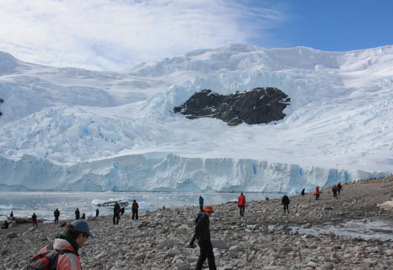 Im Vordergrund laufen Touristen in Funktionskleidung auf steinigem Strand. Im Hintergrund sieht man große Eismassen.