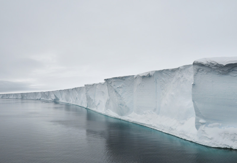 Enormous ice shelves float on the ocean, connected to a glacier onshore.